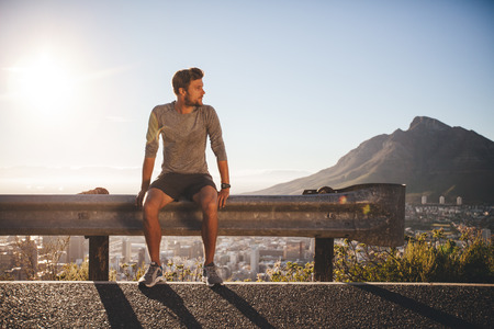 sunny day: Male runner sitting on a guardrail on country road looking away on sunny day. Young man taking a break after morning run outdoors with bright sunlight. Stock Photo