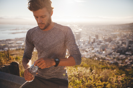 sediento: corredor joven con una botella de agua de tomar un descanso después de ejecutar duro entrenamiento al aire libre. Joven se relaja después de una carrera a punto de beber agua.