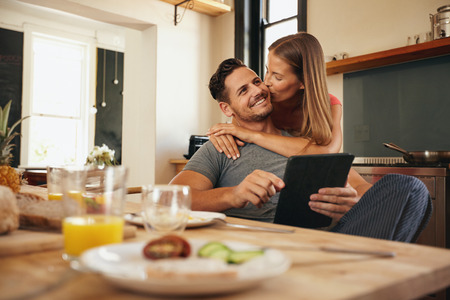 Young man holding a digital tablet while his girlfriend hugs him from behind, giving him a good morning kiss. Young love couple in morning at the kitchen. Stock Photo