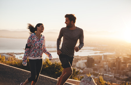 running: Pareja joven corriendo juntos al aire libre. Feliz el hombre joven y una mujer corriendo en la carretera nacional durante el amanecer. Dos personas disfrutando de correr por la mañana.