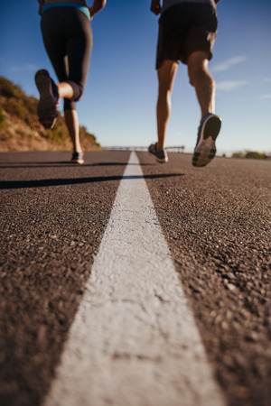 two: Cropped shot of two people running on road. Athletes training on country road. Low angle shot with focus on road.