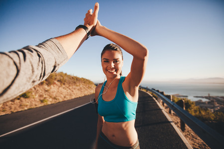 First person view of a man and woman high fiving. Happy young woman giving high five to man after outdoor training. Couple of runner on country road looking happy.