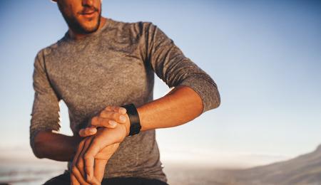 Männliche Sportler der Zeit überprüft, während auf Outdoor-Training. Junge Läufer über die Zeit auf seine Sportfeld Standard-Bild