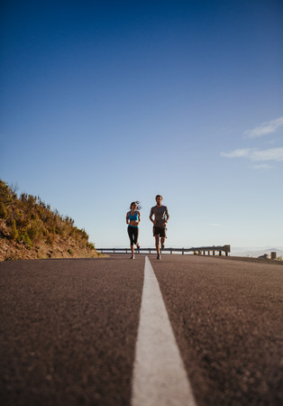 open country: Two young people jogging on country road, low angle distant shot of runners running on open road on  a summer day.
