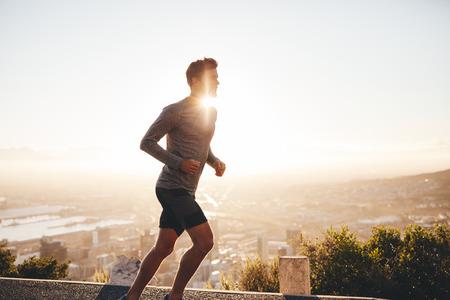 fortaleza: Entrenamiento del hombre joven en la naturaleza con el sol detrás de él. Hombre joven en la mañana de correr al aire libre.