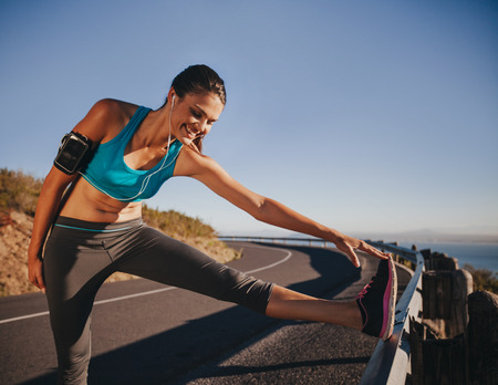 take a break: Sports woman stretching her leg on a guardrail before running outdoors. Female athlete getting ready for a run. Stock Photo