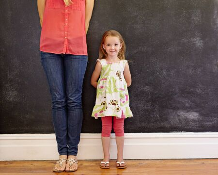little: Little girl with sweet smile standing with her mother. Mother is cropped in the picture with focus on little girl looking at camera. Both standing by a wall with copy space. Stock Photo