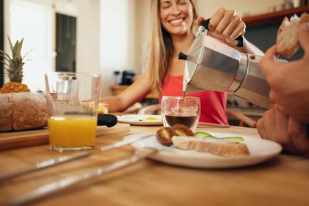 colazione: Tiro al coperto di donna versare il caffè in una tazza. Donna sorridente mentre si serve la colazione a uomo in cucina a casa. Giovani coppie che mangiano prima colazione insieme.