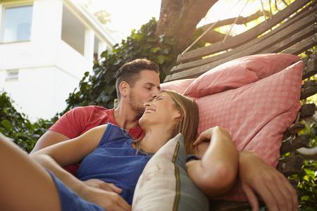 hamaca: Pareja joven está abrazando en una hamaca. Joven frente el hombre besando a su novia sonriendo. Pareja romántica al aire libre que se relaja en una hamaca.