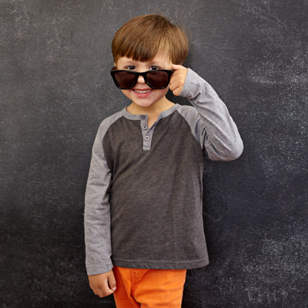 peering: Portrait of happy little boy wearing sunglasses smiling at camera. Small boy peering over his sunglasses against blackboard.
