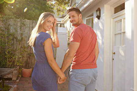 sunlit: Outdoor shot of young caucasian couple walking to their house holding hands, both looking back over shoulder and smiling at camera.