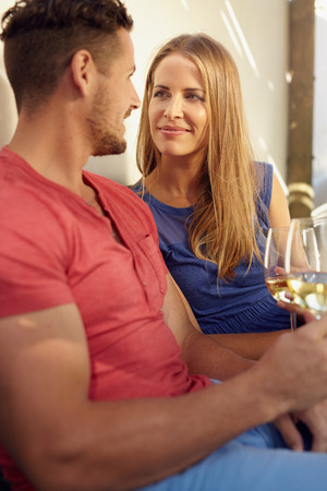 romantically: Loving young couple holding a glass of wine, looking at each other romantically.