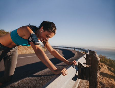 guardrail: Tired runner taking a break leaning on country road guardrail. Fit young woman athlete training outdoors.