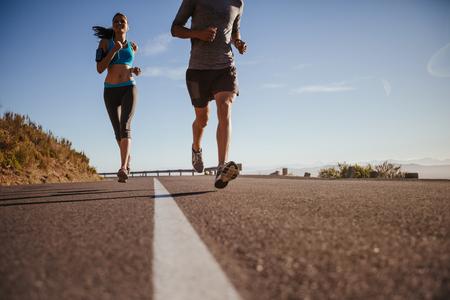 hombre deportista: El �ngulo inferior tir� de una mujer joven que se ejecutan en la carretera con el hombre delante de una ma�ana de verano. Corredores que entrenan en la carretera nacional.