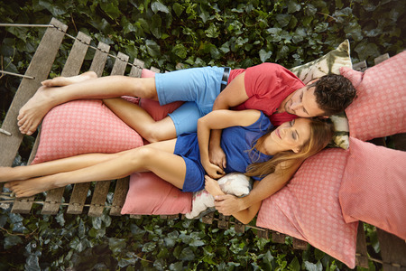 two on top: Top view of young couple lying on a garden hammock. Young man embracing his girlfriend relaxing in backyard garden. Stock Photo