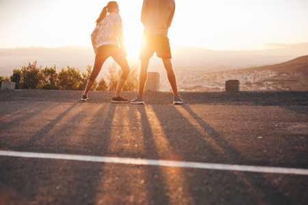 jog: Rear view of young couple standing on hillside in morning facing the sun light. Young woman stretching her legs during a running session.
