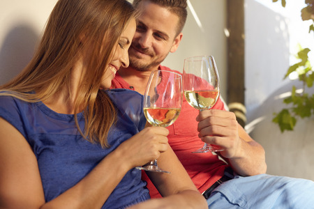 toasting wine: Happy young couple spending time in their backyard and enjoying a glass of wine. Smiling man and woman celebrating with wine, toasting wine glasses outdoors. Stock Photo