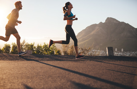 running race: Shot of young man and woman running on country road. Young couple training in nature. Stock Photo