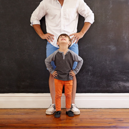 lookalike: Indoor shot of little boy looking at his father while standing in front with hands on waist.