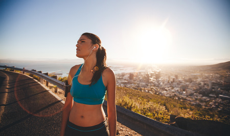 Image of young woman taking a break after hard training session on sunny day. Female athlete standing outdoors looking away. Imagens