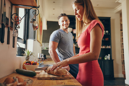 Indoor shot of young man and woman in kitchen during morning. Focus on woman cutting bread, preparing breakfast.