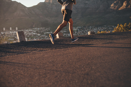 lifestyle outdoors: Low section image of young man running on country road in morning. Focus on male athlete legs.