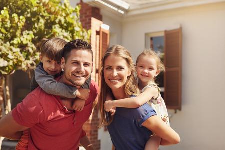 Retrato de um casal feliz carregando seus filhos em suas costas. Os pais que dão suas crianças andam às cavalitas passeios no quintal. Imagens