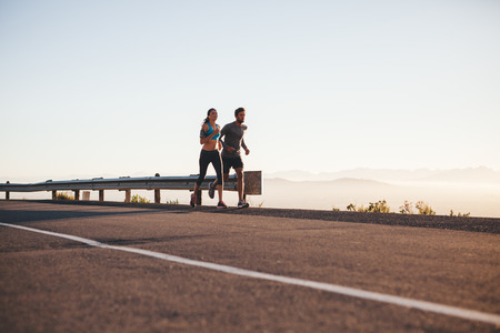 Outdoor shot of young couple on morning run. Young man and woman jogging on country road.