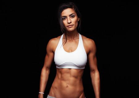 atleta: Retrato de la mujer joven del ajuste que presenta llevaba sujetador deportivo contra el fondo negro. Deportista Determinado en el estudio.