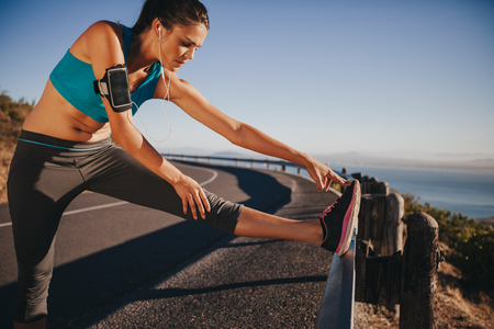 stretching exercise: Female runner stretching her legs outdoor before running. Woman doing leg stretch exercises on road guardrail.