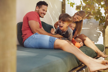 Happy family sitting together in the backyard, having fun. Father and mother playing with their kids while sitting in patio. Stock Photo