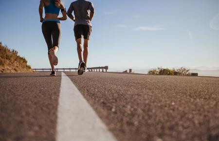 hacer footing: Vista trasera recortada tiro de dos jóvenes corriendo juntos en carretera. Hombre y mujer en correr por la mañana el día de verano. El ángulo inferior tiró de la pareja trotar al aire libre.