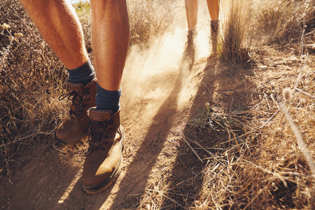 Low section shot of two young people walking on dirt trail, focus on mens hiking boots. Couple of hikers on country walk. Stock Photo