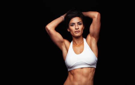 tough woman: Attractive young woman in sportswear posing on black background. Healthy female model with muscular body in studio.