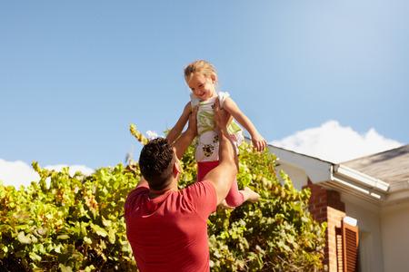 casita de dulces: Hombre joven que levanta a su hija en el aire. Padre feliz e hija jugando en su patio trasero en un día soleado.