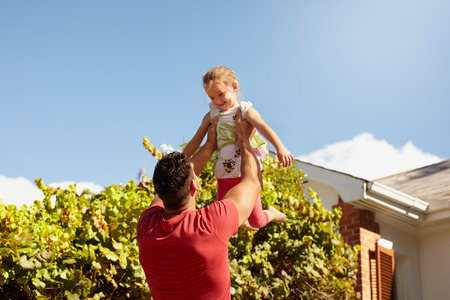 a small house: Young man lifting his daughter high in the air. Happy father and daughter playing in their backyard on a sunny day.
