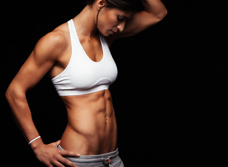 hip: Cropped shot of fit womans torso with her hands on hips. Female with perfect abdomen muscles posing on black background.