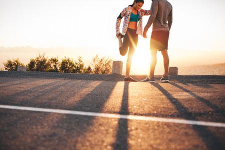 estiramientos: Tiro al aire libre de los corredores jóvenes de estiramiento antes de una carrera en la mañana. Hombre joven que se levanta y mujer estirando las piernas en la salida del sol.