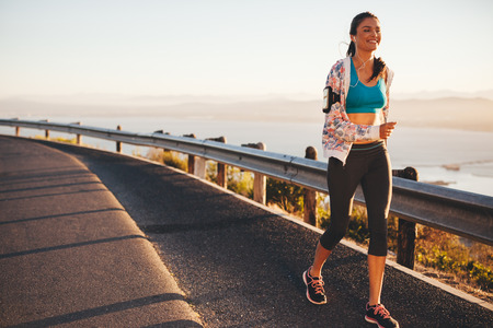 outdoor activities: Portrait of happy young woman running on country road. Caucasian female model on morning run outdoors.