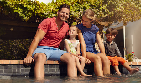 Outdoor shot of beautiful young family sitting next to swimming pool with their feet in water. Young couple with their kids enjoying a hot summer day near pool.