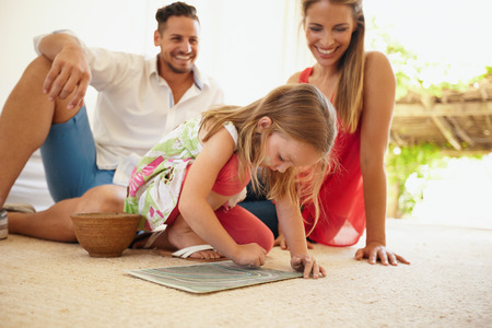 family with three children: Shot of little girl drawing picture with her parents sitting behind her in living room. Family sitting on floor with daughter painting in front. Stock Photo