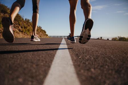 道を走ってランナーのショットをトリミングしました。人および女性の屋外ジョギングの背面ビューのクローズ アップのイメージ。道路や運動選手