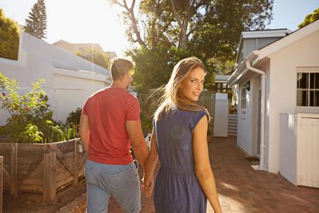 hombros: Pares jovenes que recorren en el patio trasero de la mano en la mano en un brillante día de verano, con la mujer mirando hacia atrás por encima del hombro a la cámara.