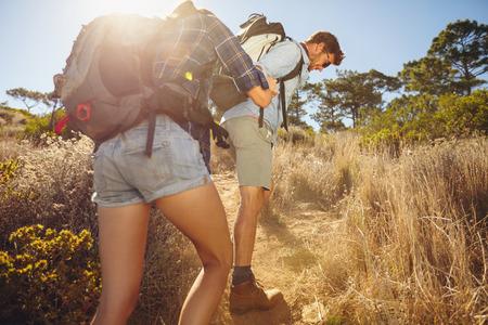 Wandelaar bergop te helpen zijn vriendin op het platteland. Paar wandelen in de bergen op een zomerse dag. Stockfoto