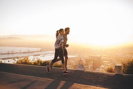 personas trotando: Foto de la joven pareja que se ejecutan en la carretera colina a las afueras de la ciudad. Hombre joven y una mujer corriendo en la mañana con la luz del sol brillante.