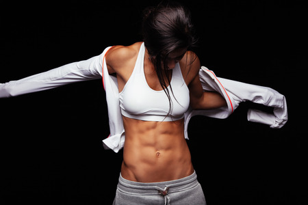 slim tummy: Image of muscular young woman wearing sports jacket. Getting ready for workout on black background