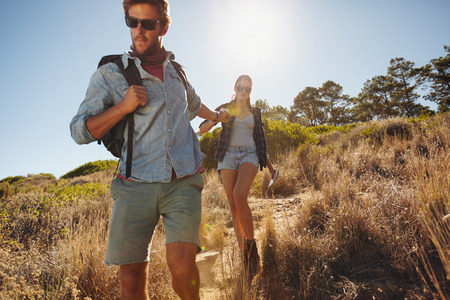 Shot of a young man on a hiking trip with his girlfriend. Young couple walking down the country trail path on a sunny day. Hikers on mountains.