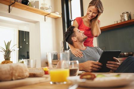 familias jovenes: Feliz pareja de jóvenes en su cocina en la mañana. Hombre sentado en la mesa de desayuno con una mesa digital con mujer de pie junto a él. Ambos buscan el uno al otro sonriendo.