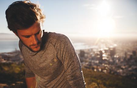 hombre deportista: Cierre de tiro de hombre joven de descanso despu�s de correr entrenamiento. Corredor al aire libre con la luz del sol brillante. Atleta relajante mirando hacia abajo despu�s de correr por la ma�ana.