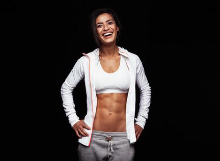 黒い背景にスポーツウェアで笑顔のスポーツウーマン。白人フィットネス モデルの腰に彼女の手で幸せを探してします。